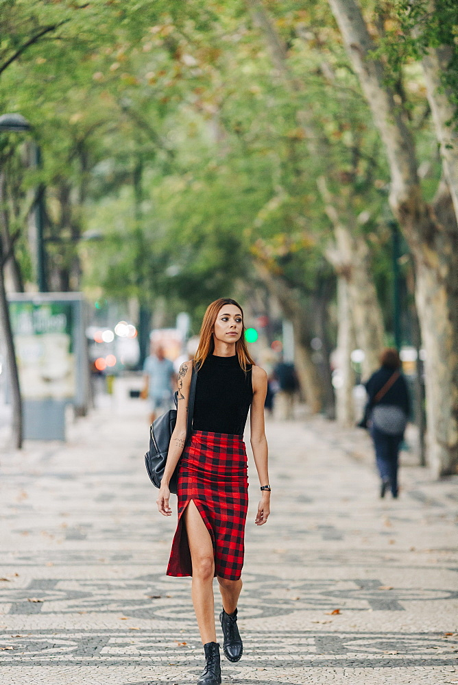 Stylish young woman walking in urban park