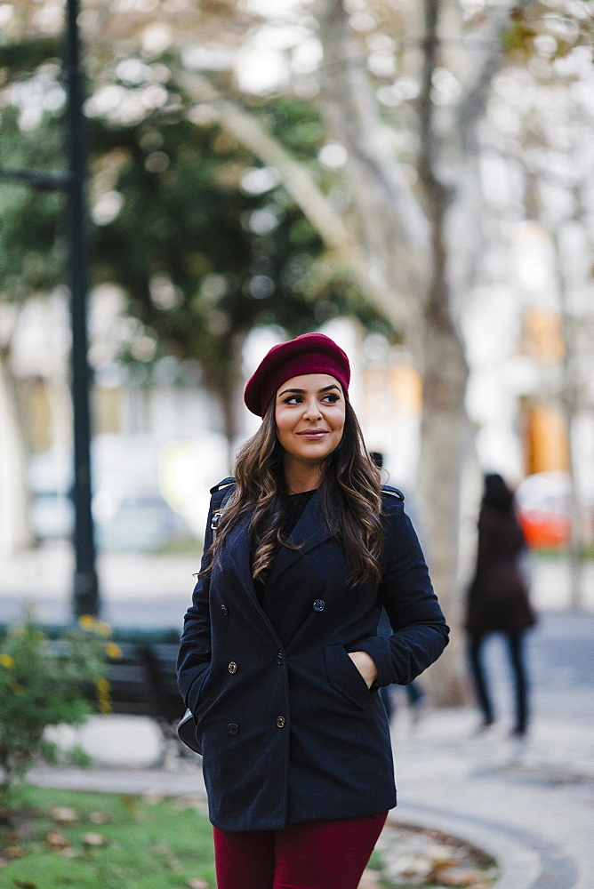 Smiling young woman in beret walking in urban autumn park