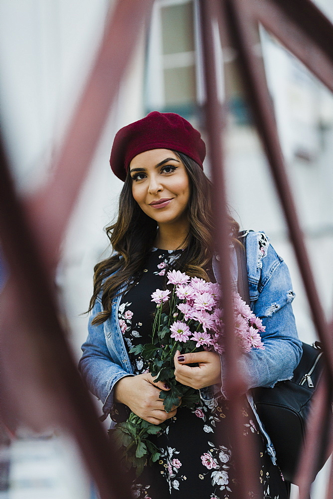 Portrait confident young woman in beret holding flower bouquet