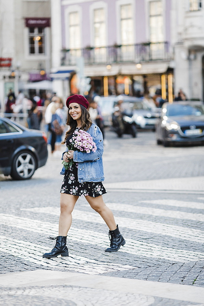 Portrait smiling young woman crossing street with flower bouquet