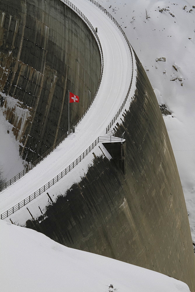 Swiss flag over snowy dam, Vals, Canton of Grisons, Switzerland