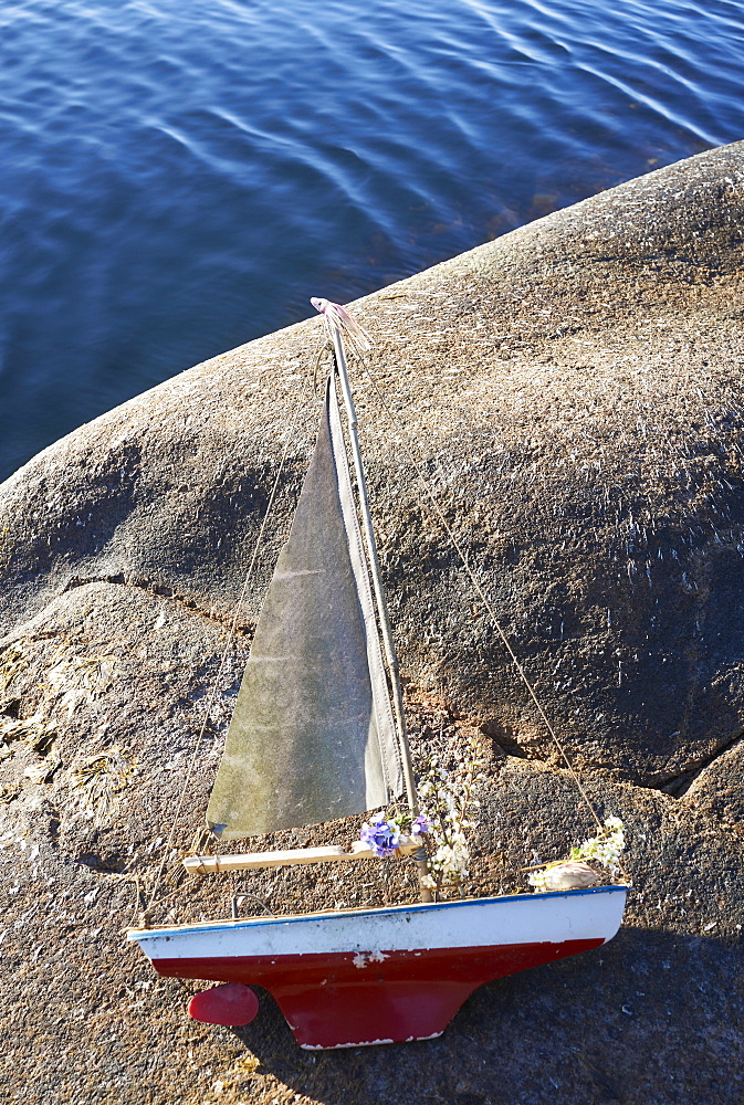 Toy sailboat with flowers on lakeside rock