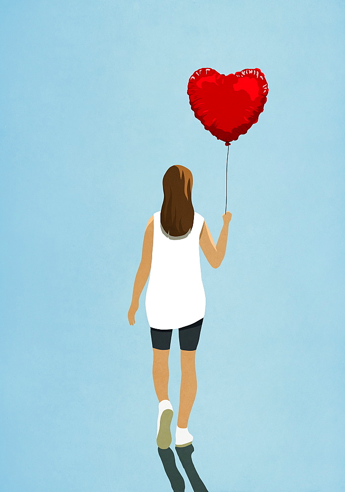 Woman carrying heart shape helium balloon