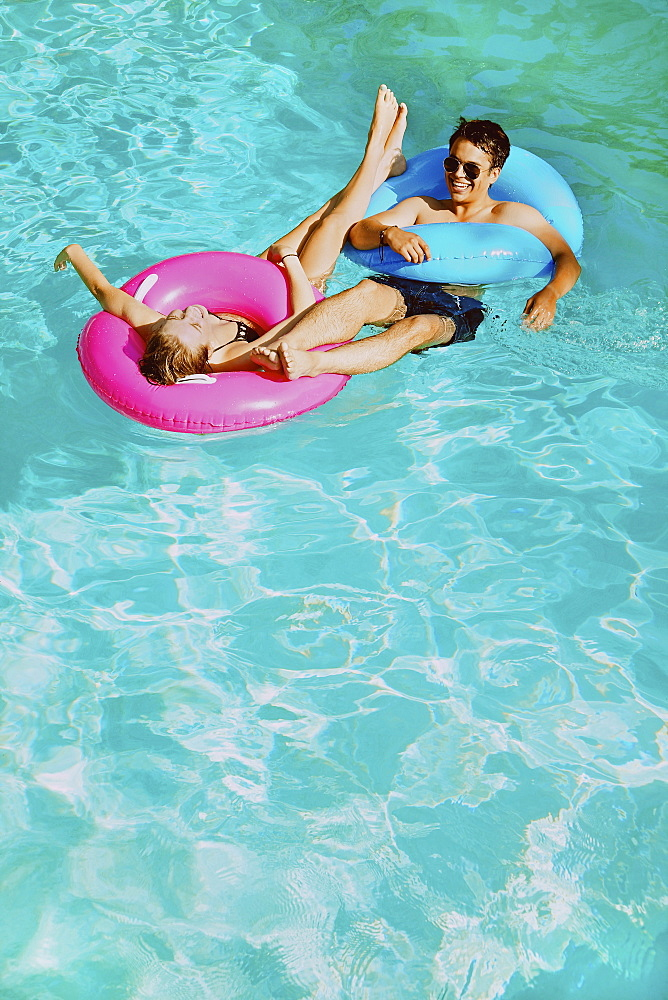 Happy young couple with inflatable rings in sunny summer swimming pool