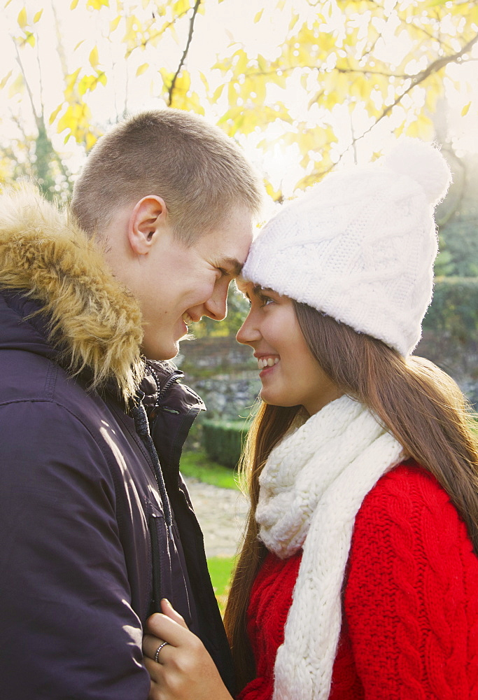 Happy teenage couple head to head in autumn park