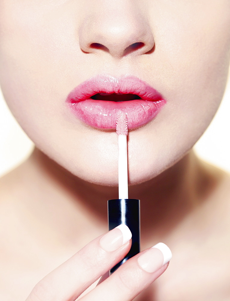 Close up woman applying lip gloss