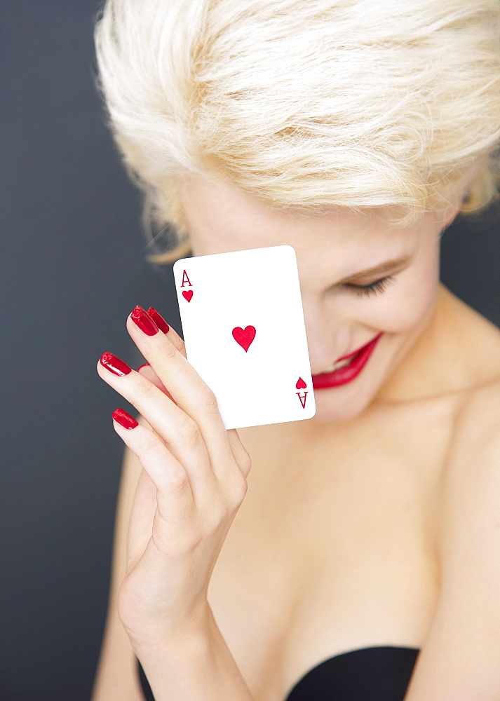 Portrait young blonde woman holding red Ace of Hearts card