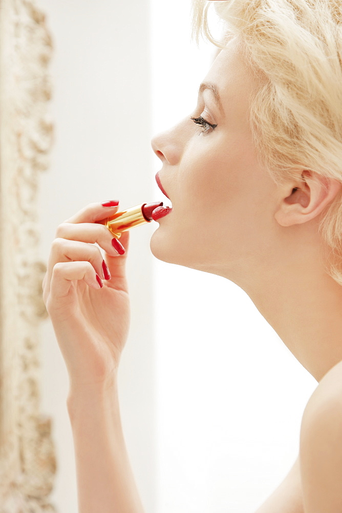 Profile glamorous young woman applying red lipstick