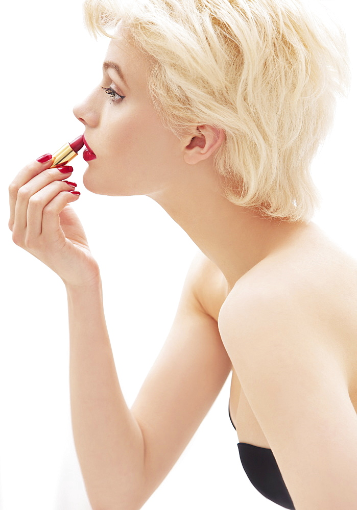 Glamorous young woman applying red lipstick