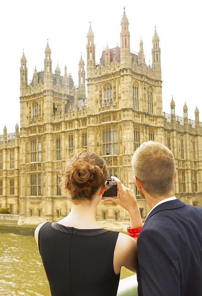 Young couple with camera photographing Houses of Parliament, London, UK - 1177-3516