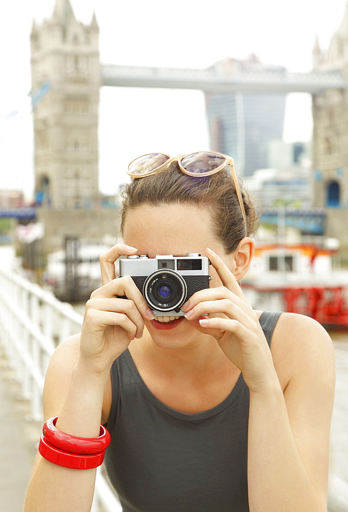 Portrait young woman with retro camera in front of Tower Bridge, London