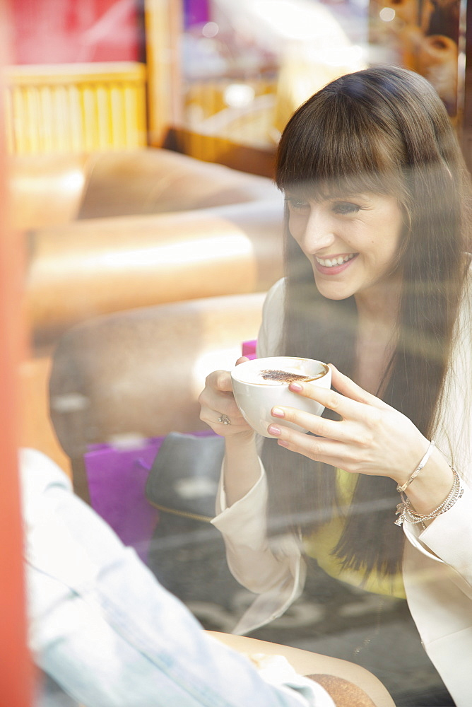 Happy young woman enjoying cappuccino in cafe window