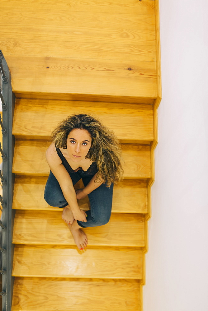 Portrait beautiful young woman sitting on wooden steps