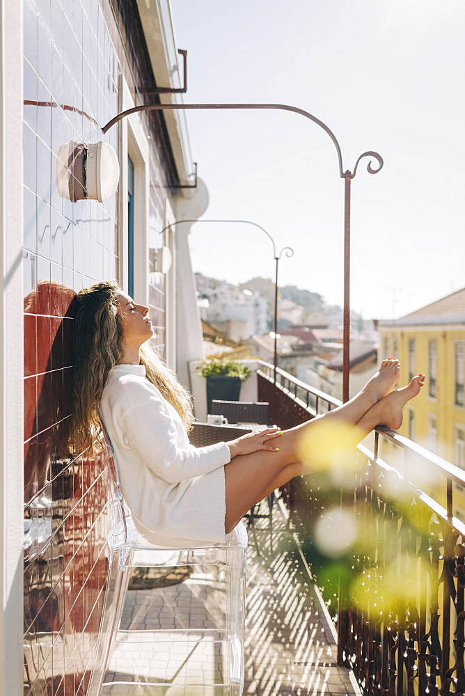Serene young woman relaxing on sunny apartment balcony, Lisbon, Portugal
