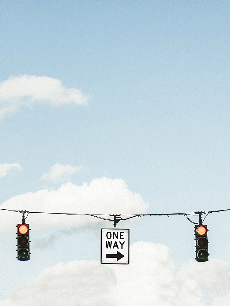 Red traffic light and one way sign below blue sky with clouds - 1177-3856