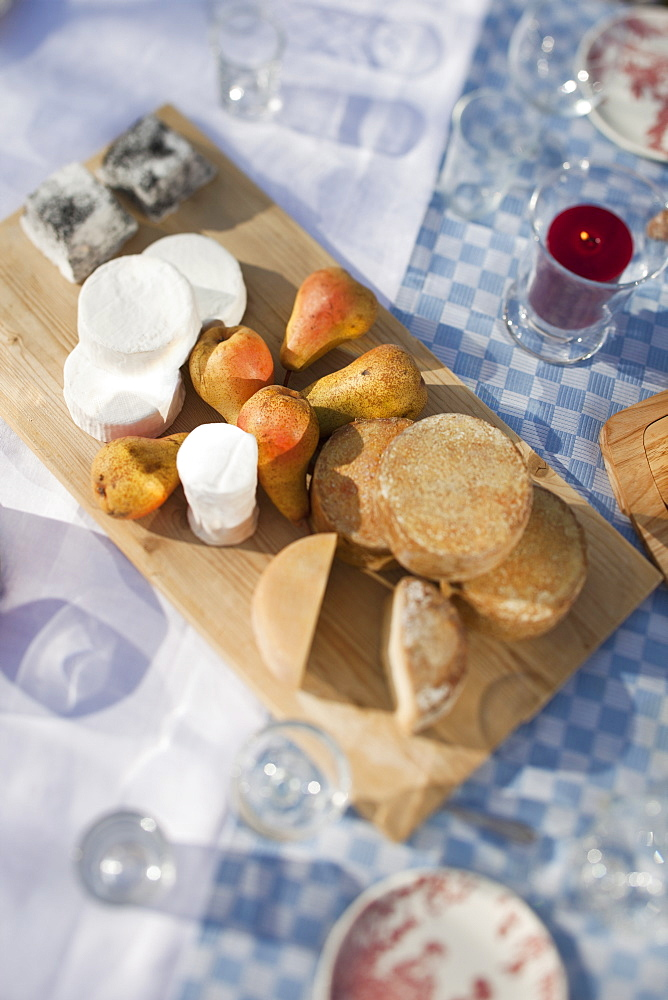 Variety of cheeses on a chopping board sitting on a table outside among glasses.