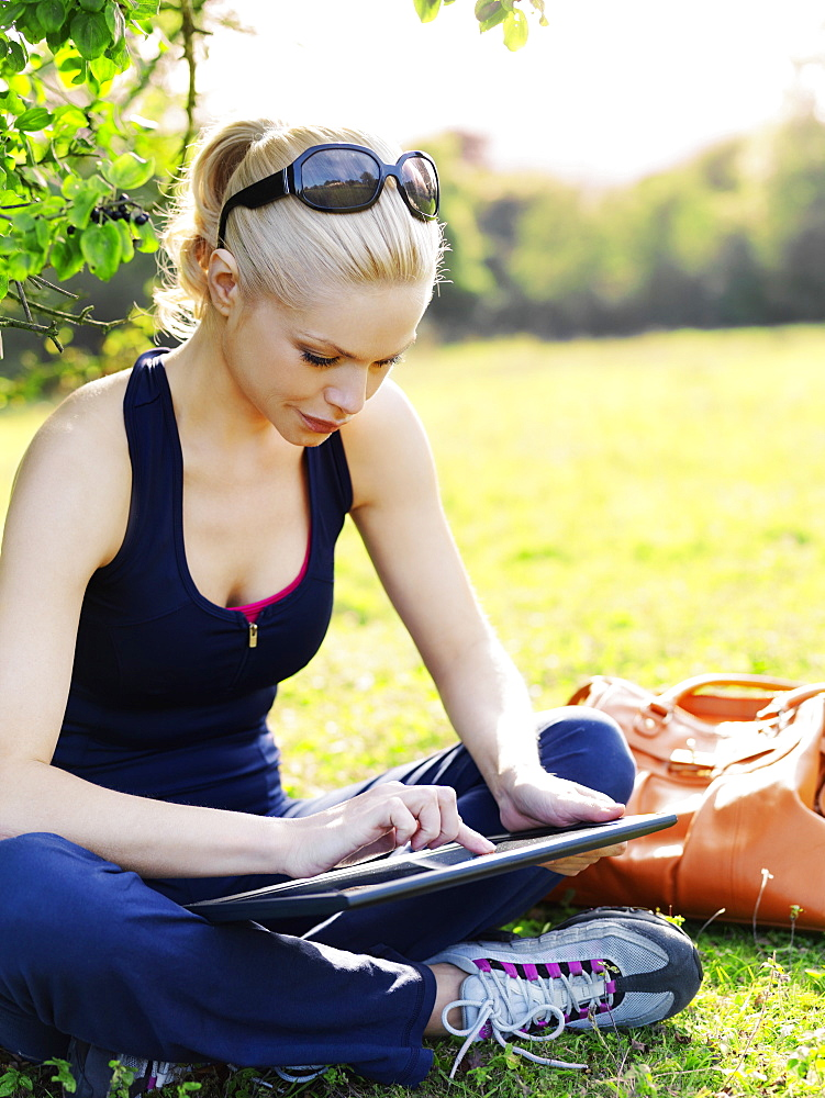 A woman in sports clothing sitting in grass using a digital tablet
