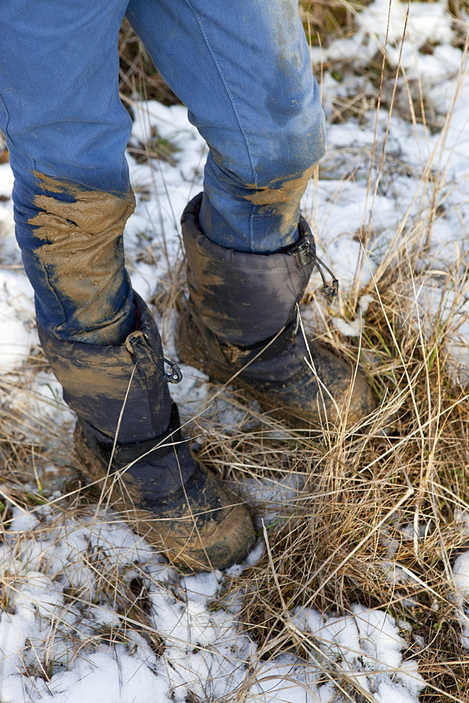 Low section of boy with dirty jeans and boots during winter