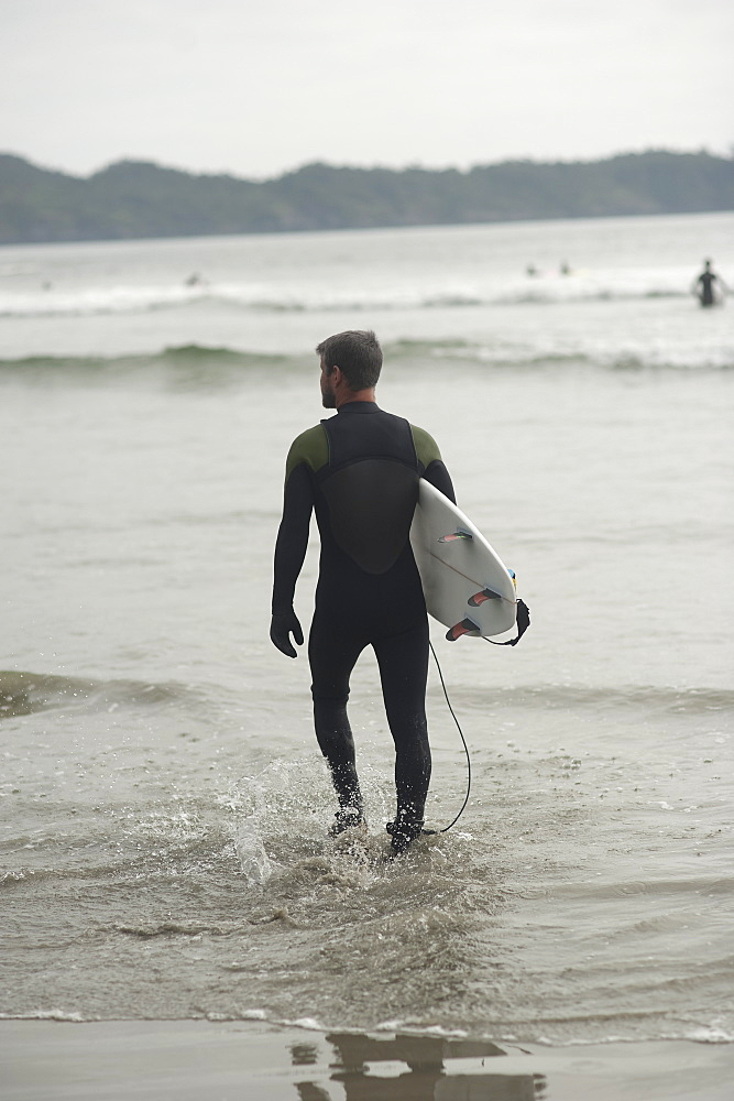 Full length rear view of man with surfboard walking in water at beach