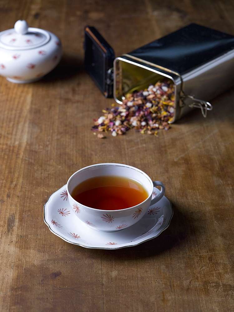 Herbal tea cup with saucer on wooden table