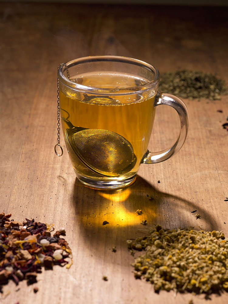 Tea strainer in cup with herbs on table