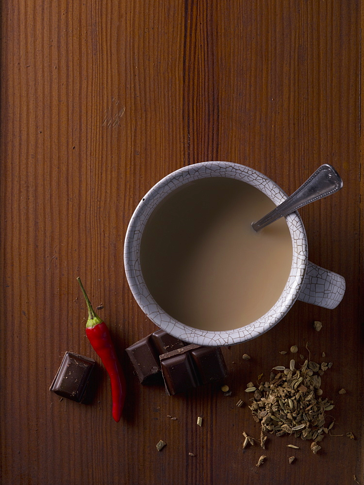 Above view of cup of coffee surrounded by chocolate, chili and spices