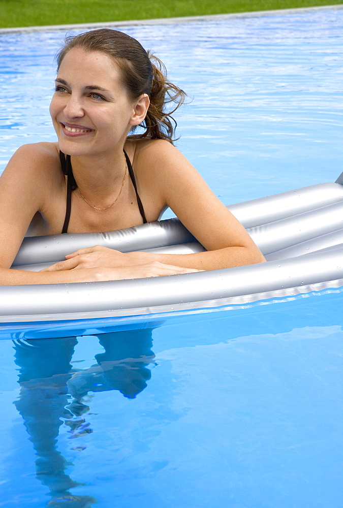 A woman relaxing on an inflatable raft in a swimming pool