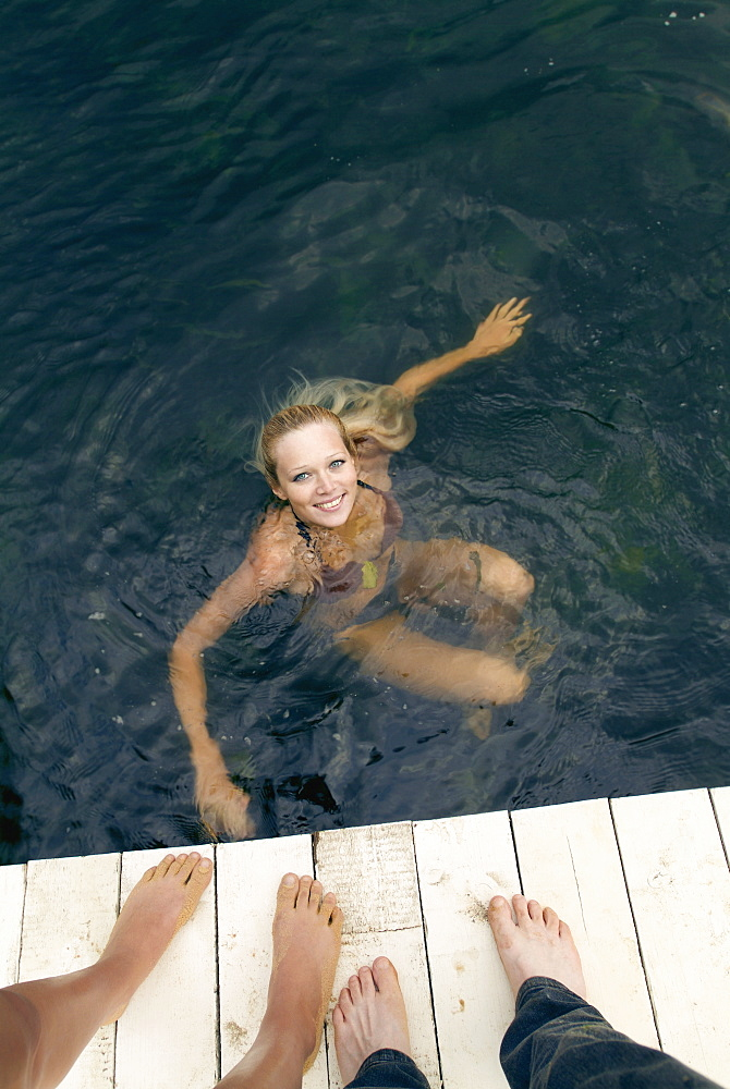 Young woman swimming and friends standing on pier