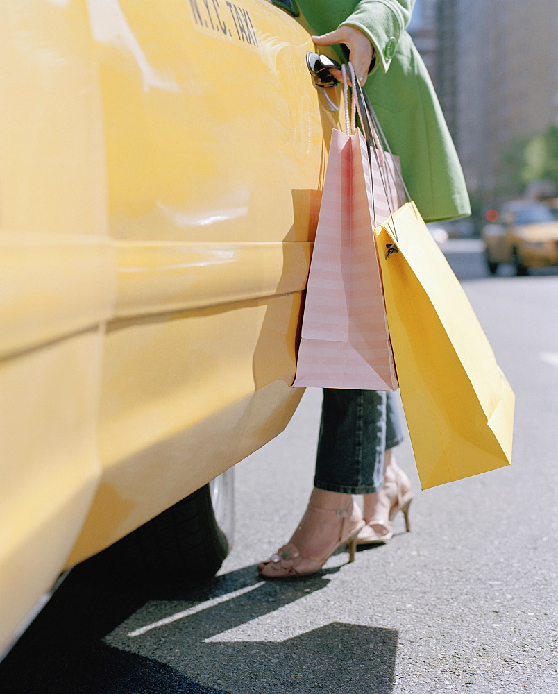 A woman holding shopping bags and opening a taxi door, new york city, usa