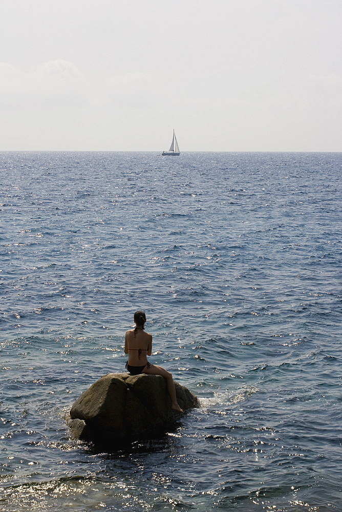 A woman sitting on a rock in the sea