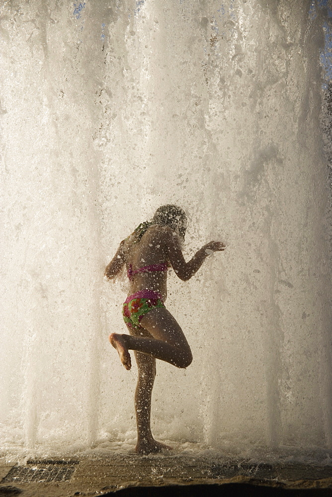 A woman standing underneath a waterfall