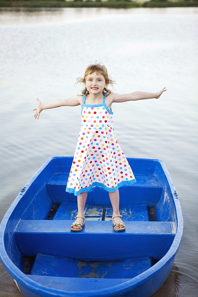 A young girl standing on a boat