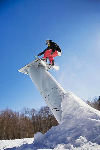 A snowboarder mid-air, stratton, vermont, usa