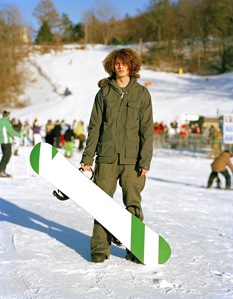 A young man standing with a snowboard at a ski resort, mountain creek, new jersey, usa