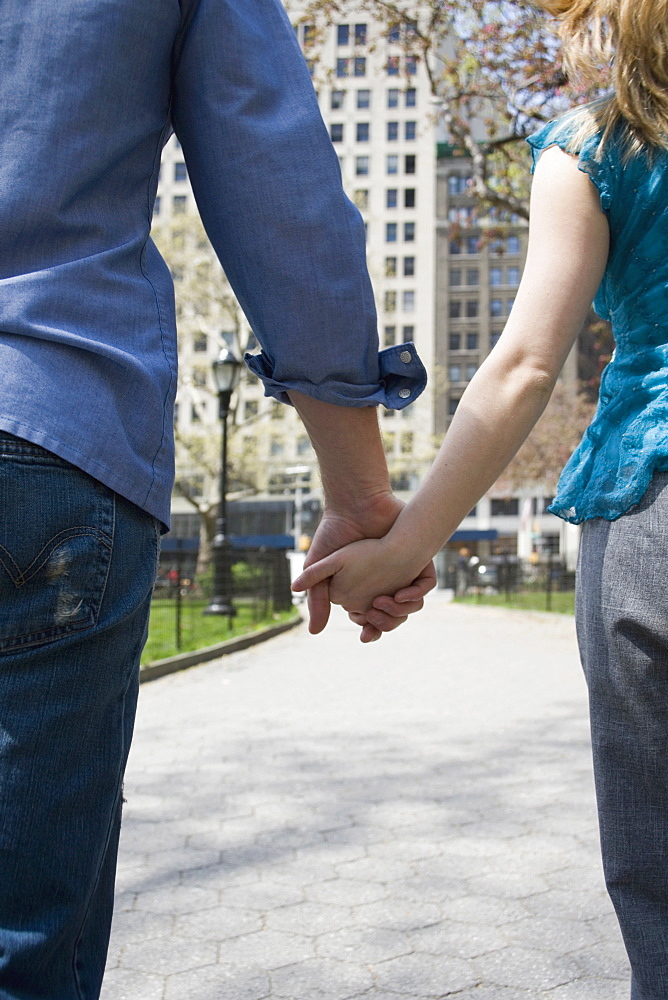 A young couple holding hands in a park, central park, new york city