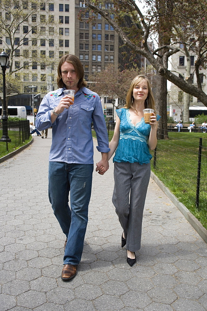 A young couple walking through a city park holding hands, central park, new york city