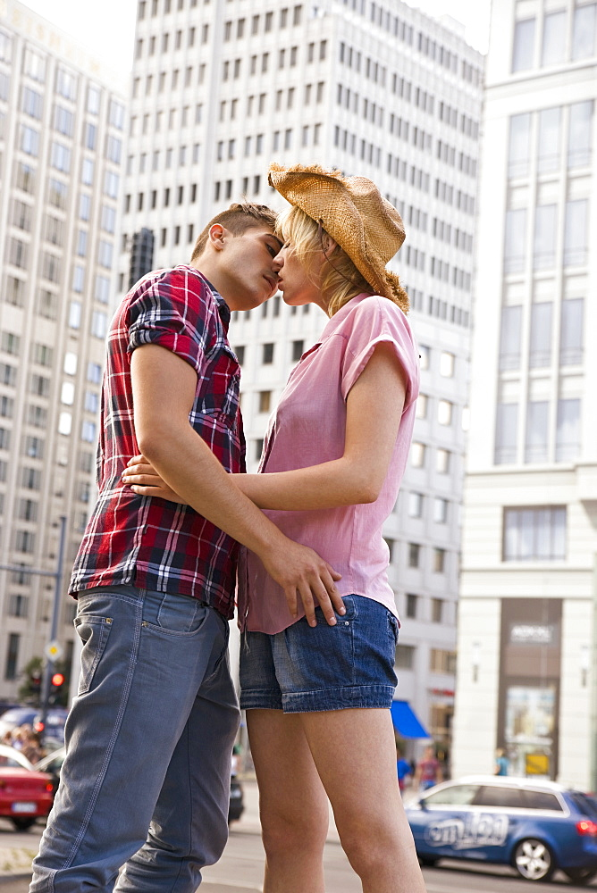 A young couple about to kiss in an urban setting