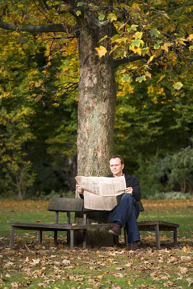 Mature man sitting on park bench reading a newspaper
