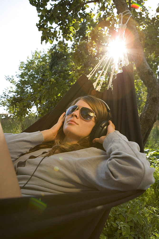 Teenager listening to music, lying in hammock
