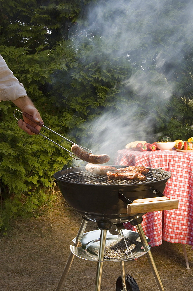Man cooking meat on a barbeque grill