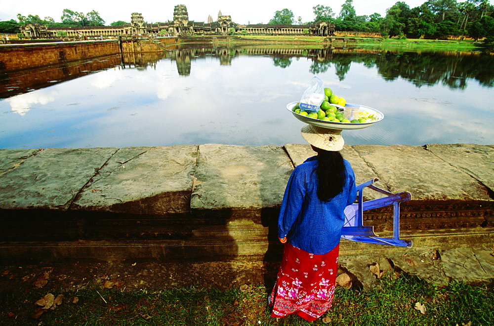 Rear view of a female vendor carrying lime fruit on her head, Angkor Wat, Angkor, Siem Reap, Cambodia