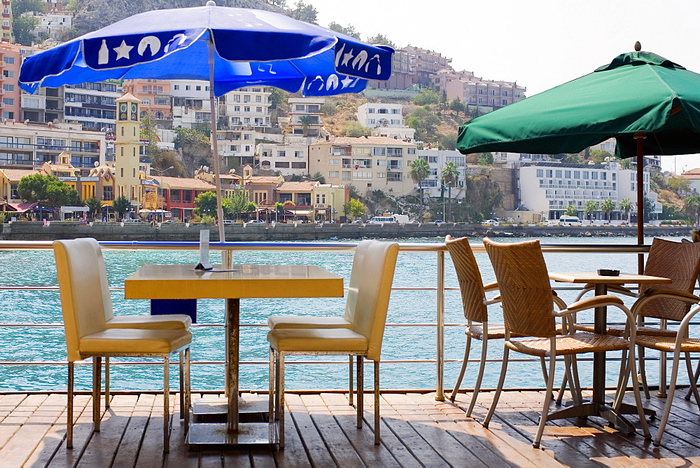 Empty chairs and tables in a restaurant with buildings in the background, Ephesus, Turkey