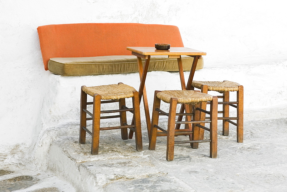 Empty table with three stools in a restaurant, Mykonos, Cyclades Islands, Greece