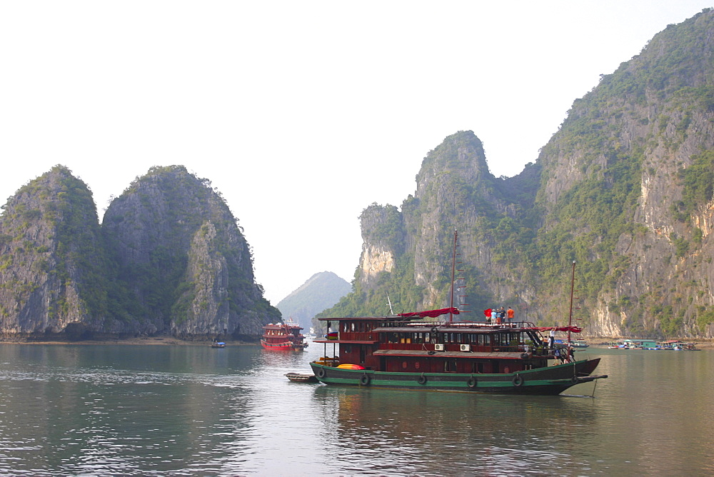 Tourboats in a bay rock formations in the background, Halong Bay, Vietnam