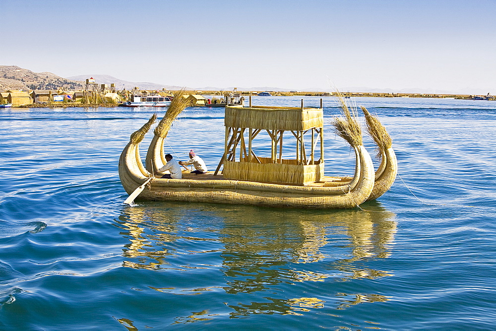 Two men rowing a reed boat, Lake Titicaca, Uros Floating Islands, Puno, Peru