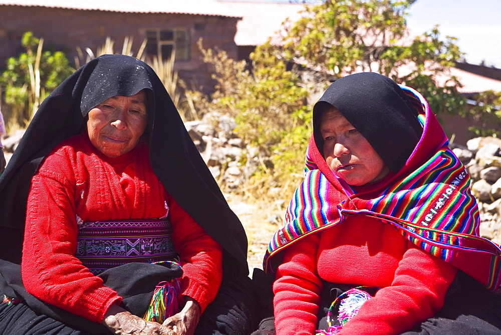 Close-up of two mature women taking part in a wedding ceremony, Taquile Island, Lake Titicaca, Puno, Peru
