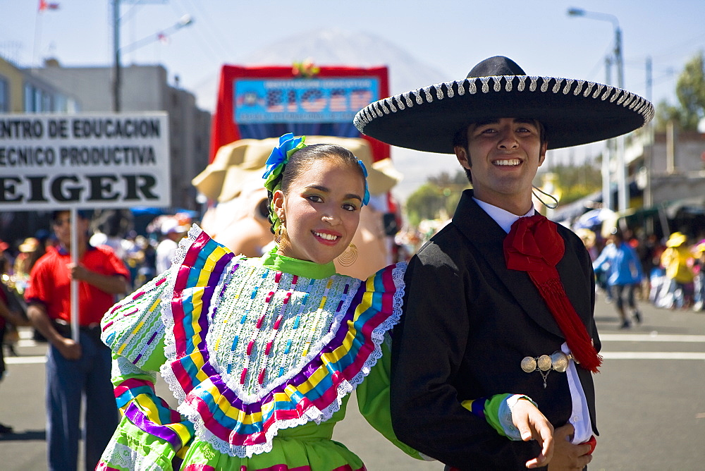 Portrait of a young couple with arm in arm in a parade, Arequipa, Peru