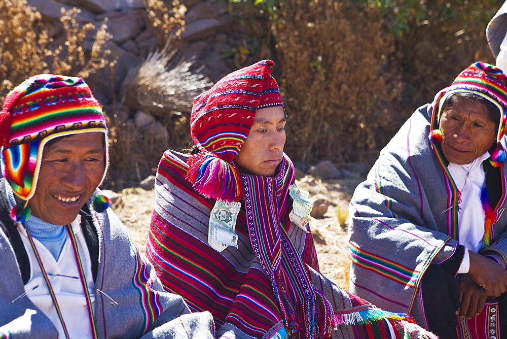 Mature man and a young man sitting with a groom, Taquile Island, Lake Titicaca, Puno, Peru