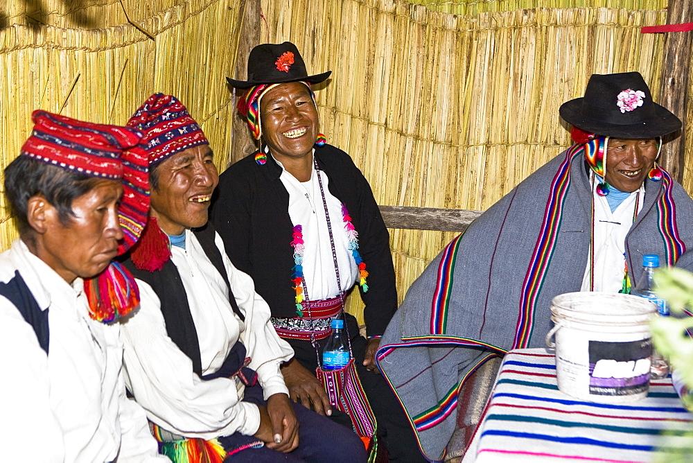 Four people sitting and smiling, Lake Titicaca, Taquile Island, Puno, Peru
