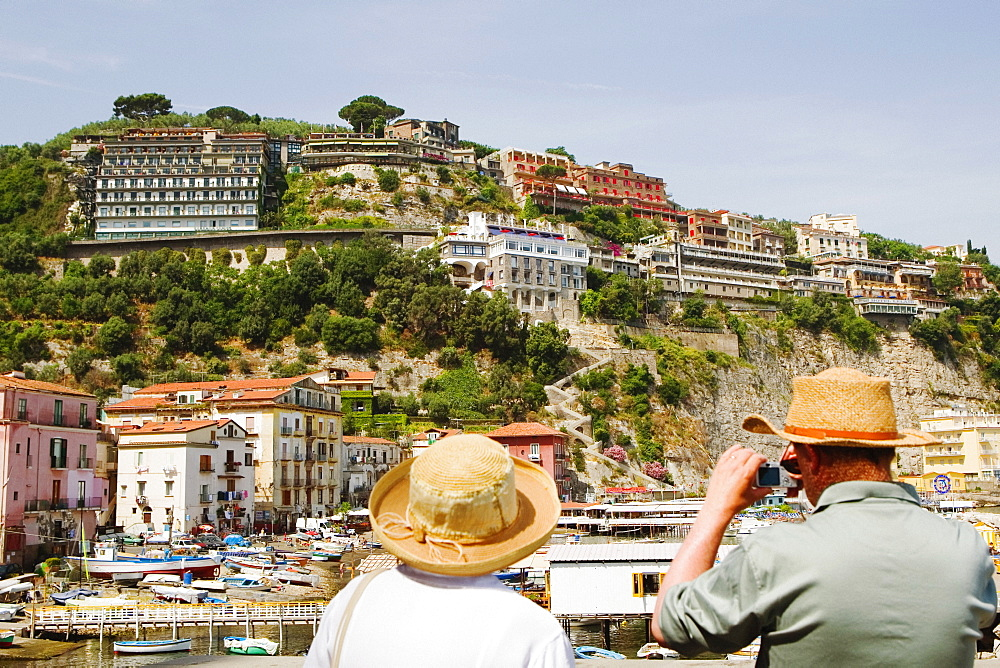 Rear view of tourists photographing a harbor, Marina Grande, Capri, Sorrento, Sorrentine Peninsula, Naples Province, Campania, Italy